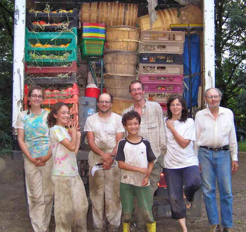 Henry's family and staff in front of Henry's truck filled with vegetables and ready to go to the Evanston Market